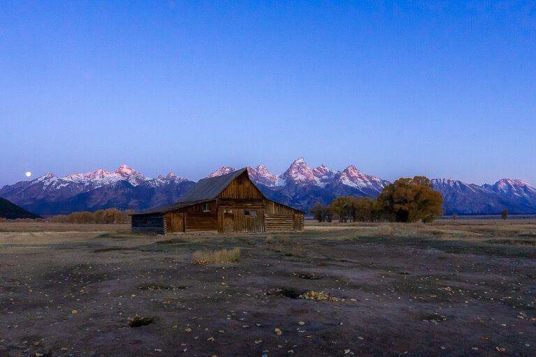 TA Moulton Barn at civil twilight dawn before sunrise with moon disappearing over teton range