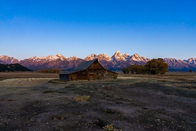 Mountains glowing red with wooden building in shadow