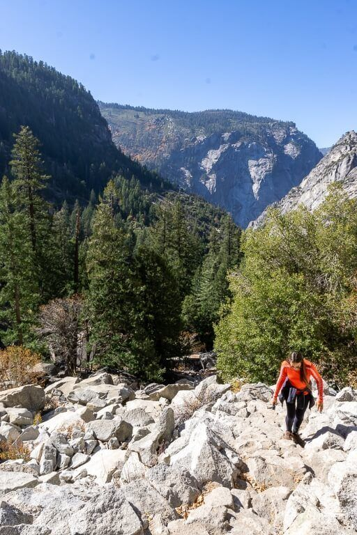 Kristen hiking up rocks on switchbacks with awesome valley behind