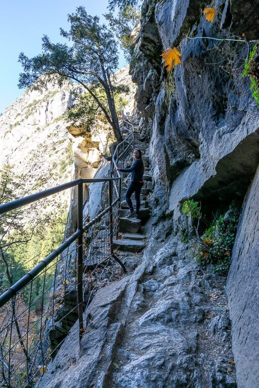 Kristen climbing a steep narrow section of hiking trail on the way to vernal fall mist trail hike yosemite national park