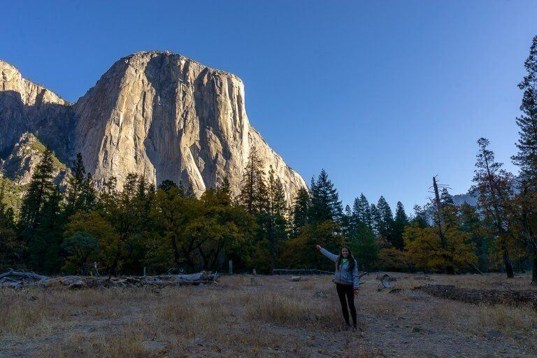 Kristen pointing at El Capitan from a meadow in yosemite national park at sunrise