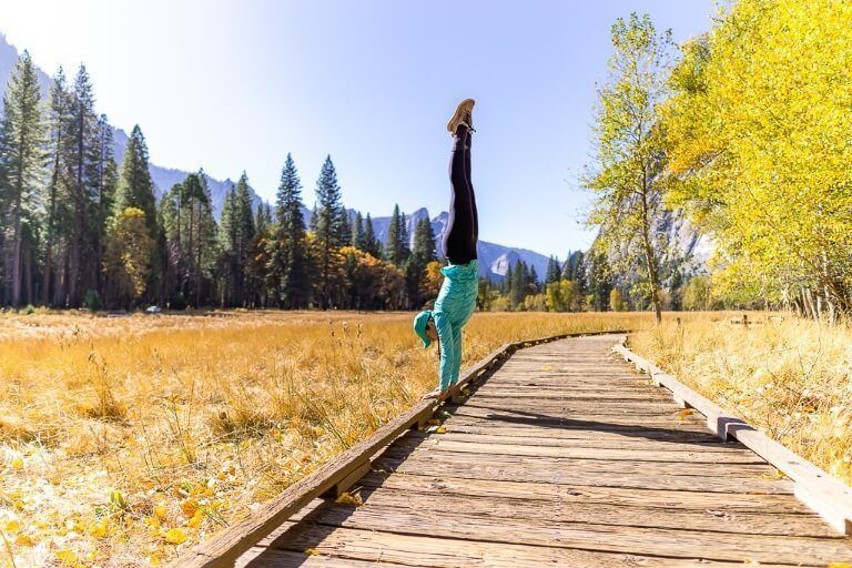 Kristen nailing a perfect handstand on a wooden boardwalk in Yosemite national park cooks meadow loop trail fantastic photography
