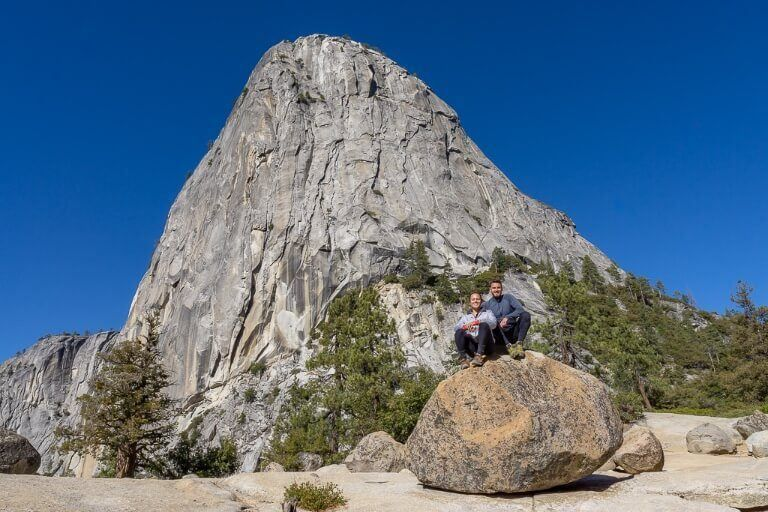 Mark and Kristen sat on a boulder with towering Liberty Cap behind in Yosemite National Park photography from Mist trail