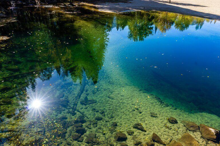 Starburst of the sun reflecting in deep and shallow water in california