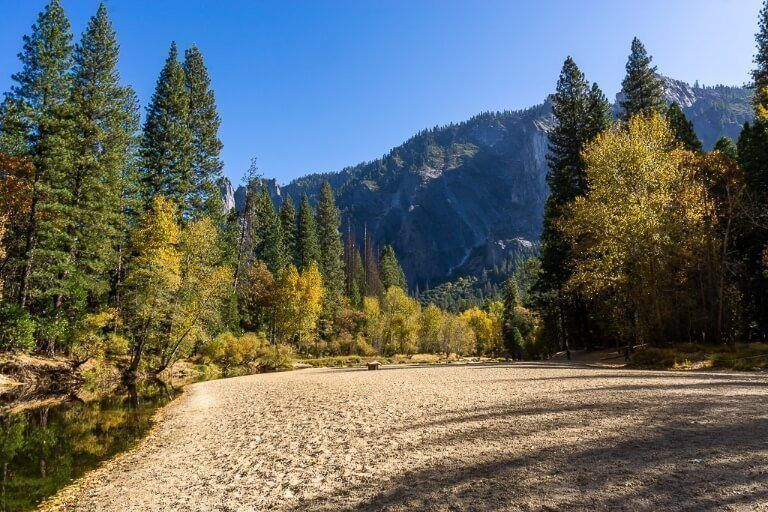 Sandy beach along river with trees and blue sky in stunning valley
