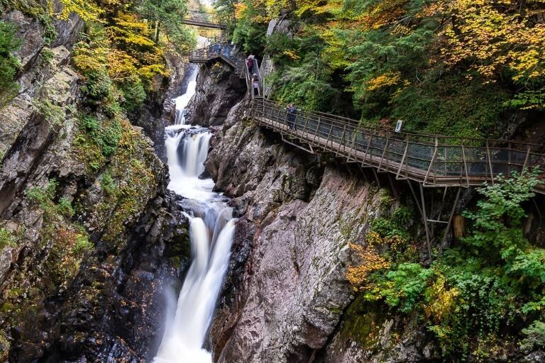 Beautiful narrow gorge waterfall high falls gorge in lake placid ny close to whiteface mountain wooden boardwalks and bridges with colorful trees