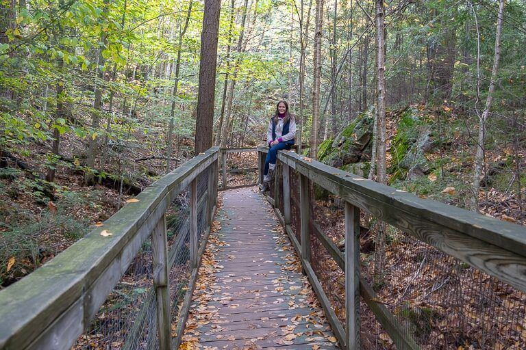 Woman sat on fence of boardwalk through forest