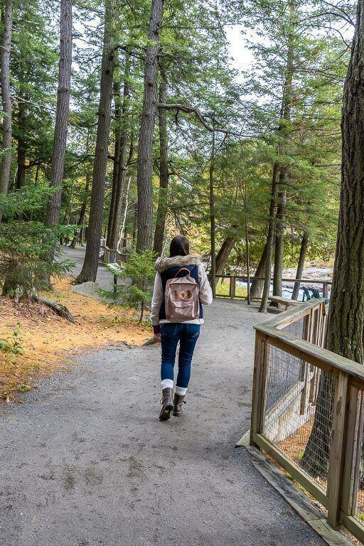Woman walking through forest on path next to river in new york