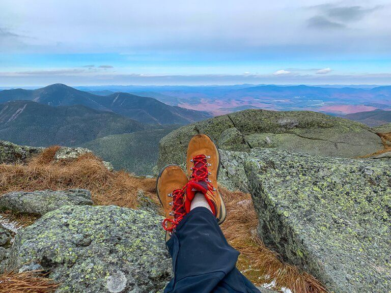 Womans hiking boots with rocks and views from the summit of a mountain in new york high peaks