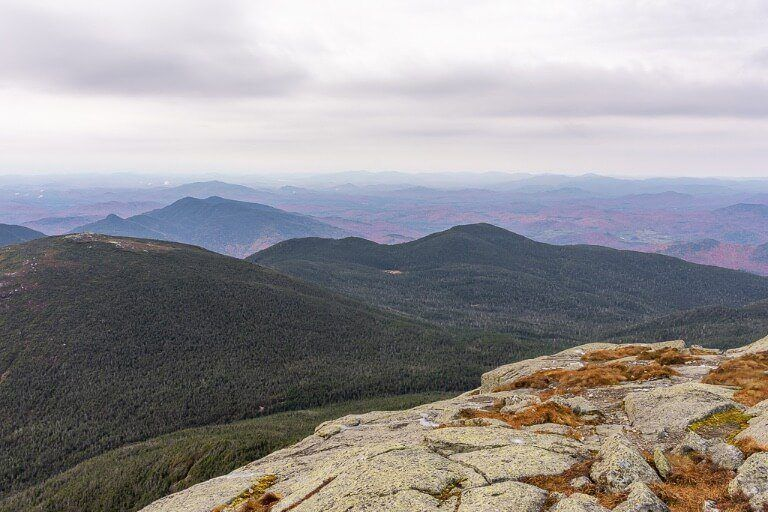 Fall foliage colors just about visible among the grey misty clouds from the top of adirondack mountains ny