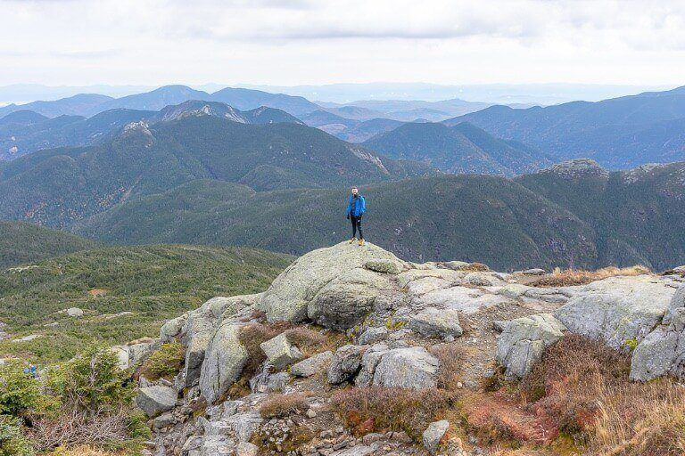 Man standing on distant rock for perspective to show to scale of views from the summit of mount marcy the highest of the high peaks in adirondacks new york near lake placid
