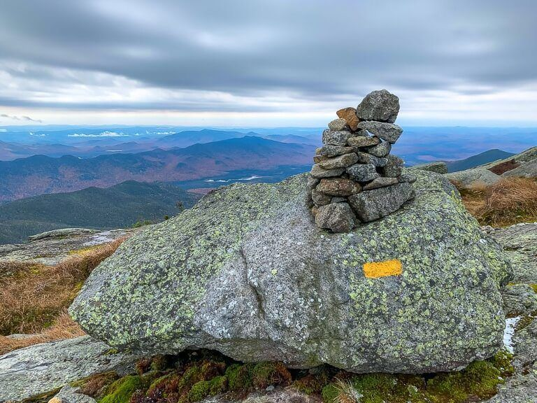 Cairns piles of rocks marking the trail to Mount Marcy summit and the highest point in new york with clouds and views of rolling hills