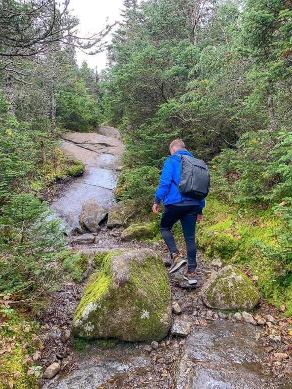 Man on trail with boulders and trees in adirondacks new york with blue coat and peak design backpack and adidas terrex free hikers