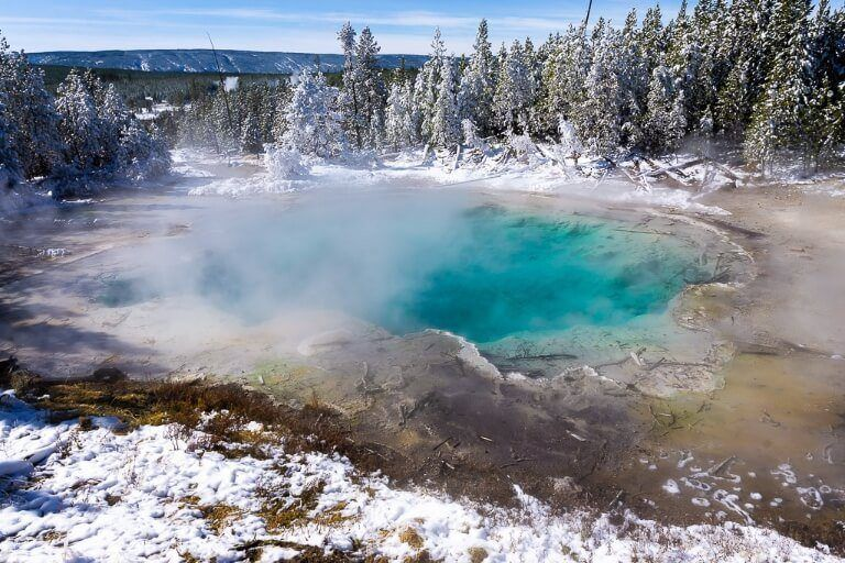 Turquoise hot spring pool surrounded by snow and trees