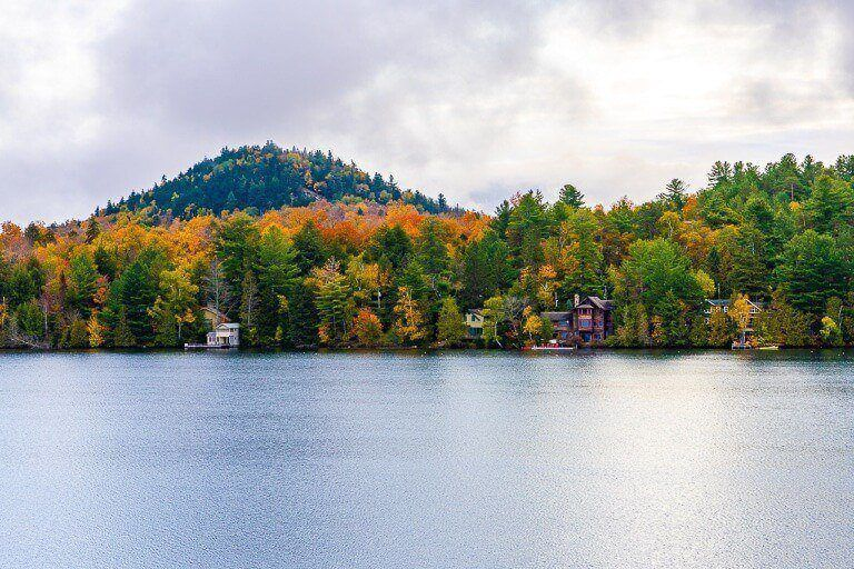 Beautiful Photograph of Mirror Lake with colorful Fall Foliage on a cloudy day best things to do in lake placid include hiking around the lake