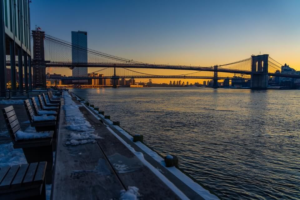Benches looking out into river from Pier 17 in New York City with orange sky