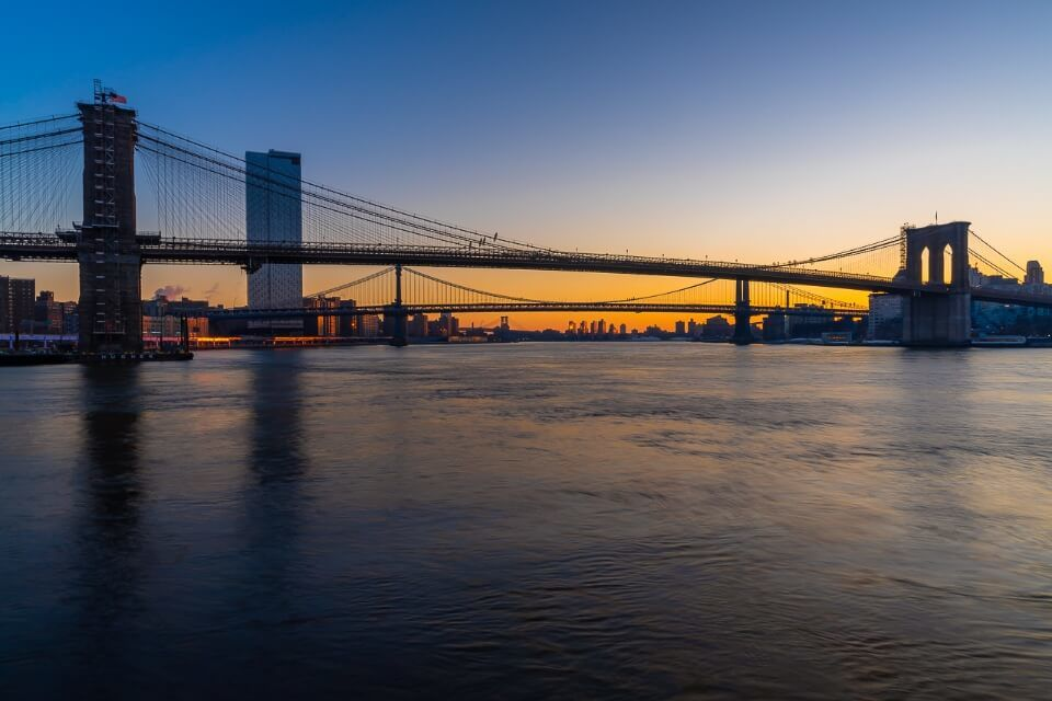 Beautiful photograph of Brooklyn Bridge and Manhattan Bridge from Pier 17 in New York City at dawn just before sunrise orange sky and smooth river