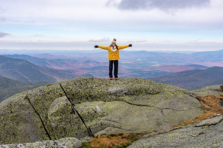 Hiking Mount Marcy in the Adirondacks Mountains New York spectacular views from the summit with woman outstretched arms celebrating climbing the hike to reach the top of the highest high peak