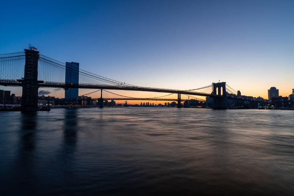 Brooklyn Bridge as seen from Pier 17 at sunrise in New York City