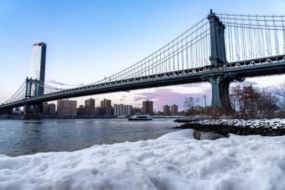 NYC Manhattan Bridge with snow foreground taken from brooklyn pebble beach walk over the long bridge when visiting new york city