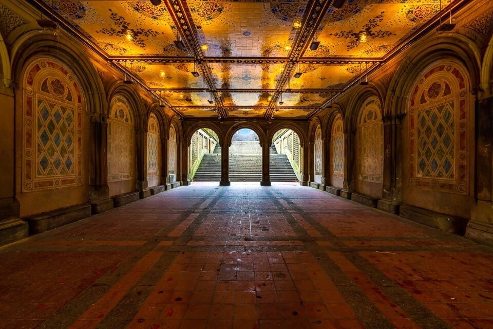 Bethesda Terrace glowing orange reflecting tiled ceiling in Winter Central Park NYC one of the best things to do epic photography location