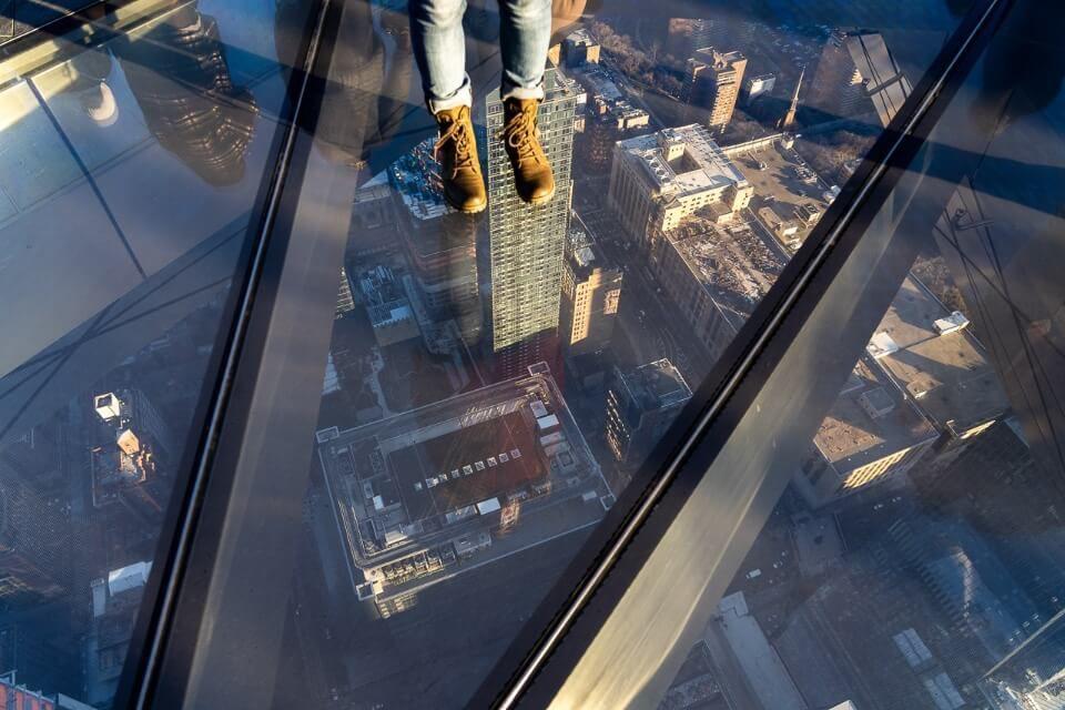 Looking down through glass floor at roads and buildings below