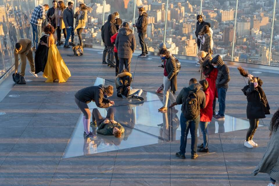 Tourists taking photographs in a glass corner and on a glass bottomed floor in new york city