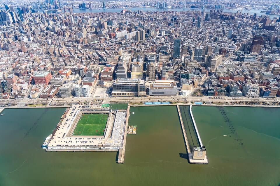 Manhattan skyline with soccer pitch in hudson river and tunnel vent