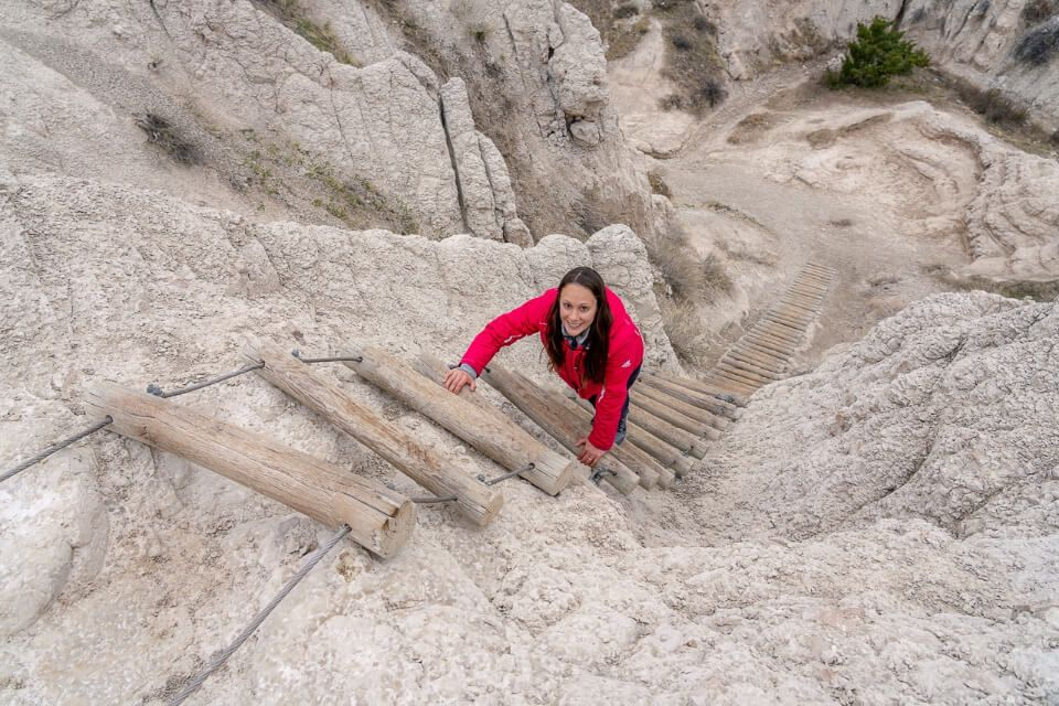 Smiling woman climbing up wooden ladder poles on the notch trail in badlands national park sd