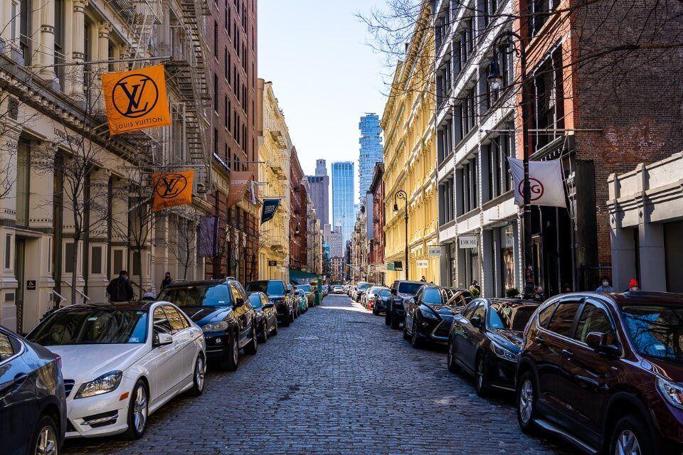 SoHo cobblestone street with upmarket shopping cars parked on roadside