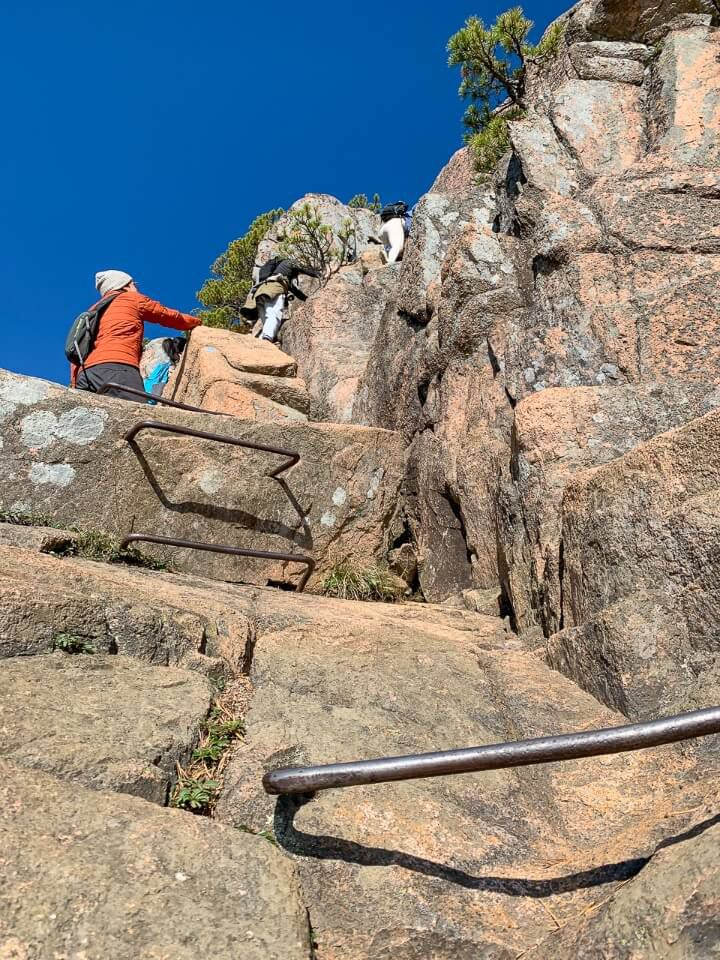 Steep gradient of a climb with iron ladders to assist and crowds of people waiting