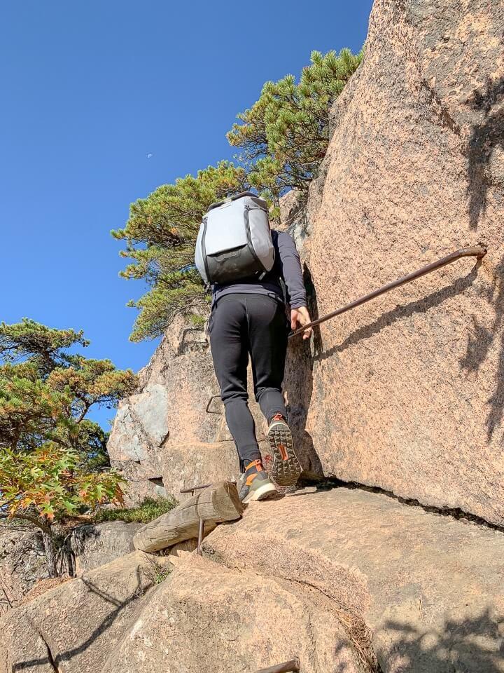 Man climbing along narrow rock edge holding onto iron run bars on beehive trail hike in acadia national park