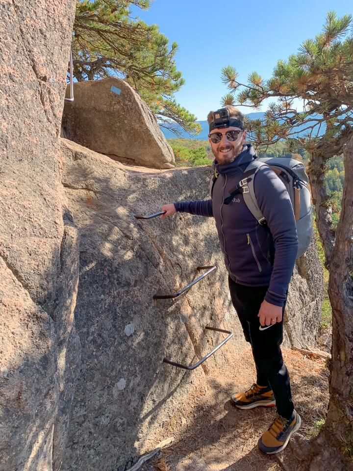 Man starting the first iron rung ladder climb on the Beehive Trail in Acadia National Park