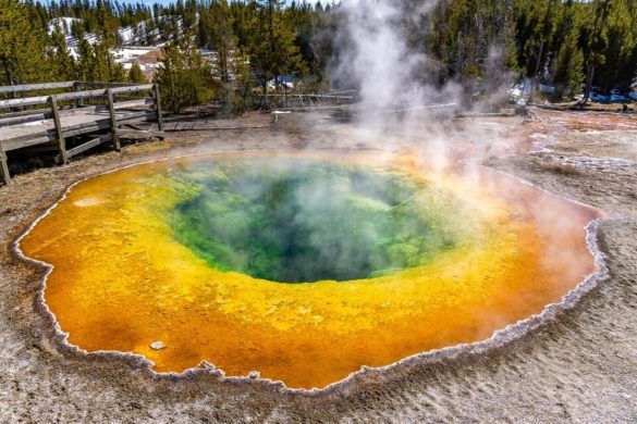 Best Things To Do In Yellowstone National Park Morning Glory Pool Stunning vibrant colors oranges yellows greens and blacks with steam billowing