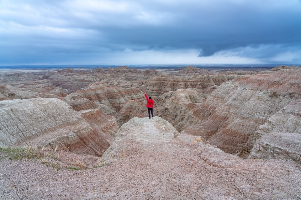 Badlands national park stunning landscape wide angle with dark rain clouds and woman raising hand in air