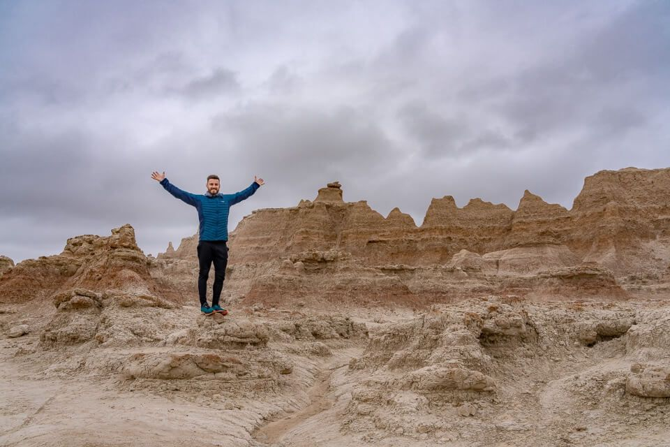 Badlands national park is one of the best things to do near mount Rushmore on a south dakota road trip man with arms stretched out on door trail with badlands wall