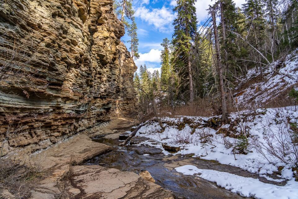 Spearfish canyon scenic byway is an amazing and underrated place to visit near mount rushmore river running through tall narrow wall canyon with snow
