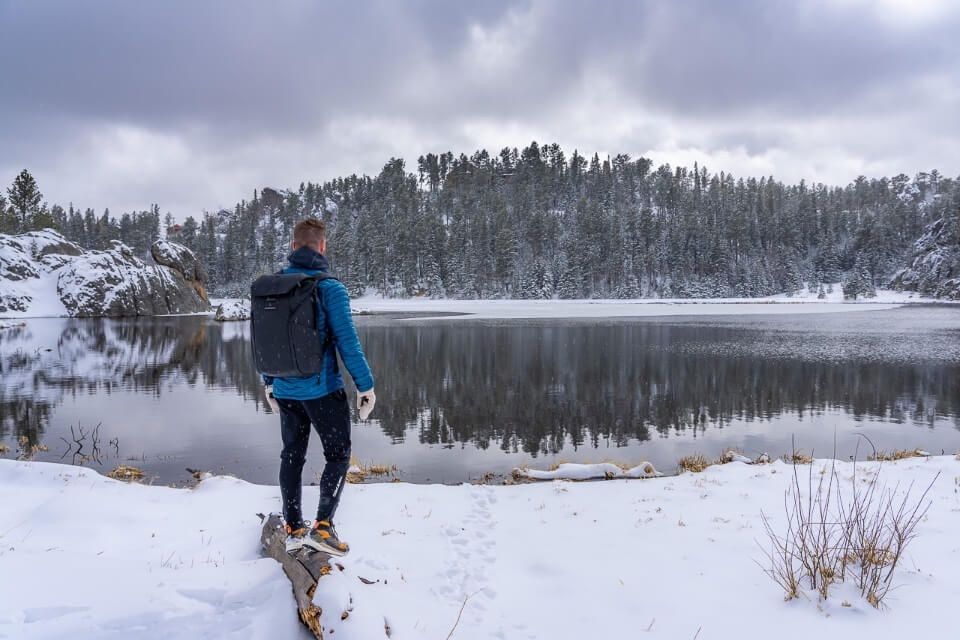 Man standing on log covered in snow with lake surrounded by ice and snow in south dakota sylvan lake