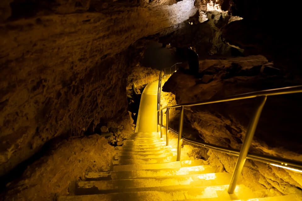 Wind Cave national park stairs illuminating yellow in the cave one fo the best things to do near mount Rushmore south dakota