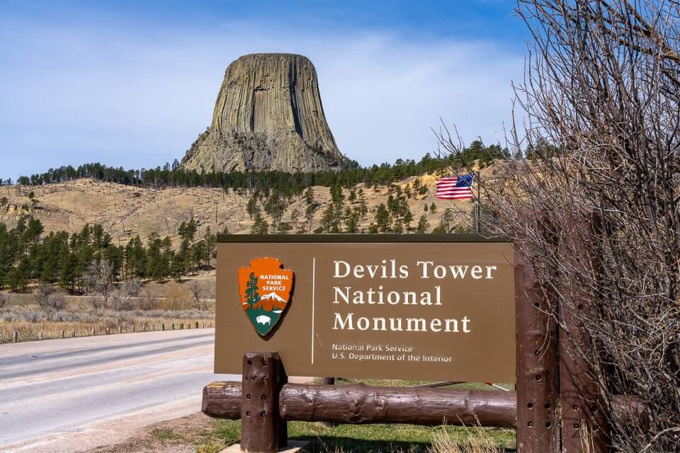 Entrance to national monument in wyoming sign and rock formation in background