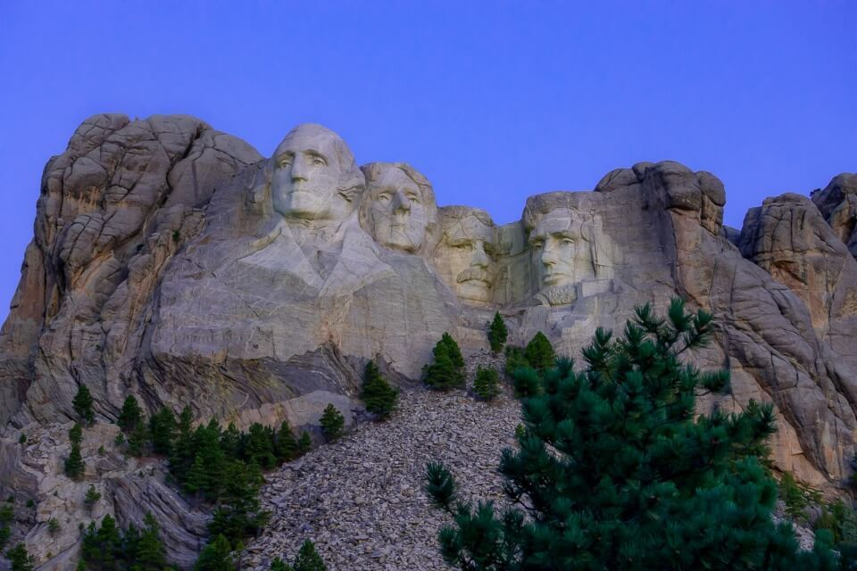Mount Rushmore National Memorial before sunrise with purple sky