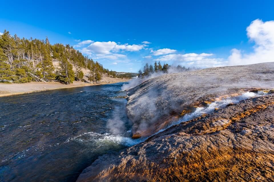 Firehole river with small hot waterfall near grand prismatic spring midway geyser basin best things to do in yellowstone national park