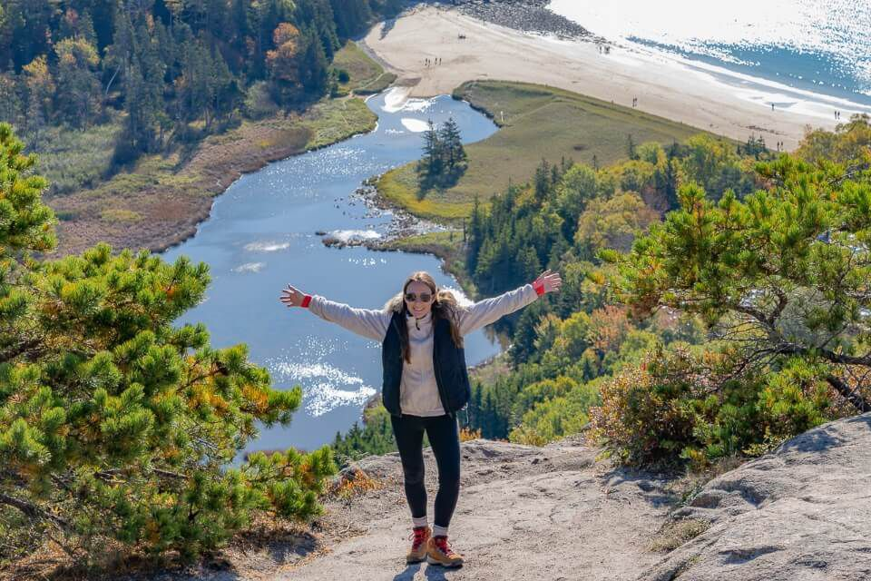 Celebrating being at the top of Beehive Trail climb ladders and drop offs with view over sand beach from the summit