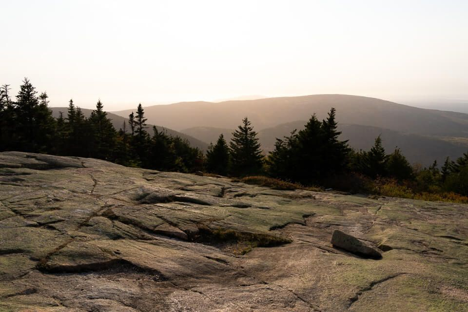 Watching sunset on a hazy day from the top of Cadillac Mountain in Bar Harbor Maine is one of the best things to do in acadia national park