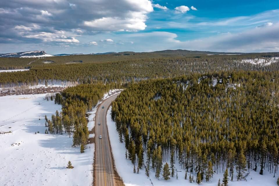 Drone shot of route dissecting a forest covered in snow