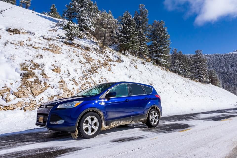 Car on snow near yellowstone national park road trip planner resource and how to plan the perfect road trip