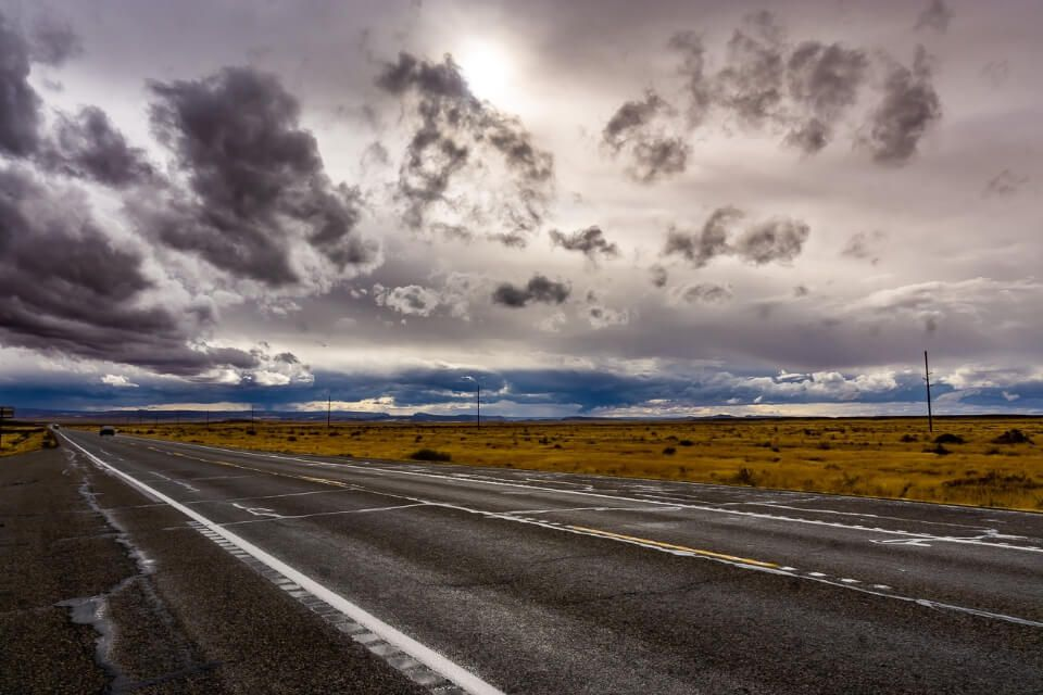 Cloudy sky with sun on a road in utah near arches national park tips on how to plan a road trip