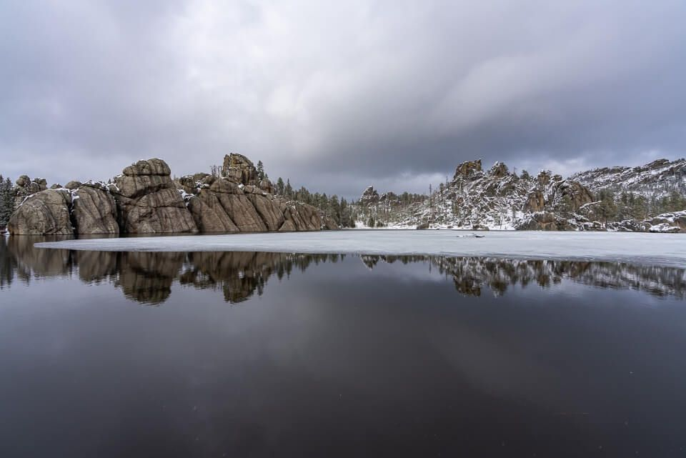 Sylvan Lake reflecting on still water with blowers and snow and ice