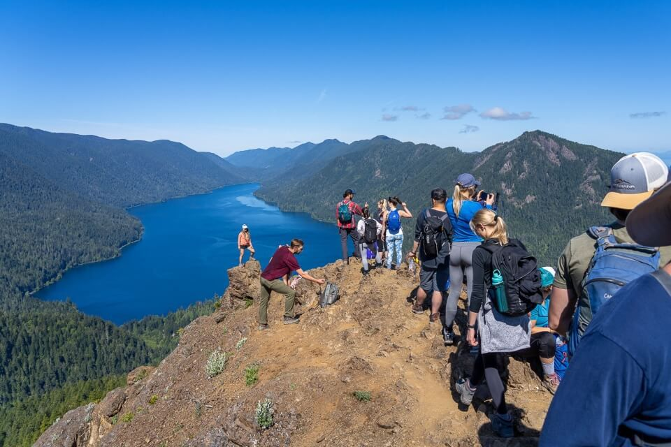 Best things to bring on a day hike backpacks layers sun protection various hikers at the summit of Mount Storm King in Olympic National Park Washington