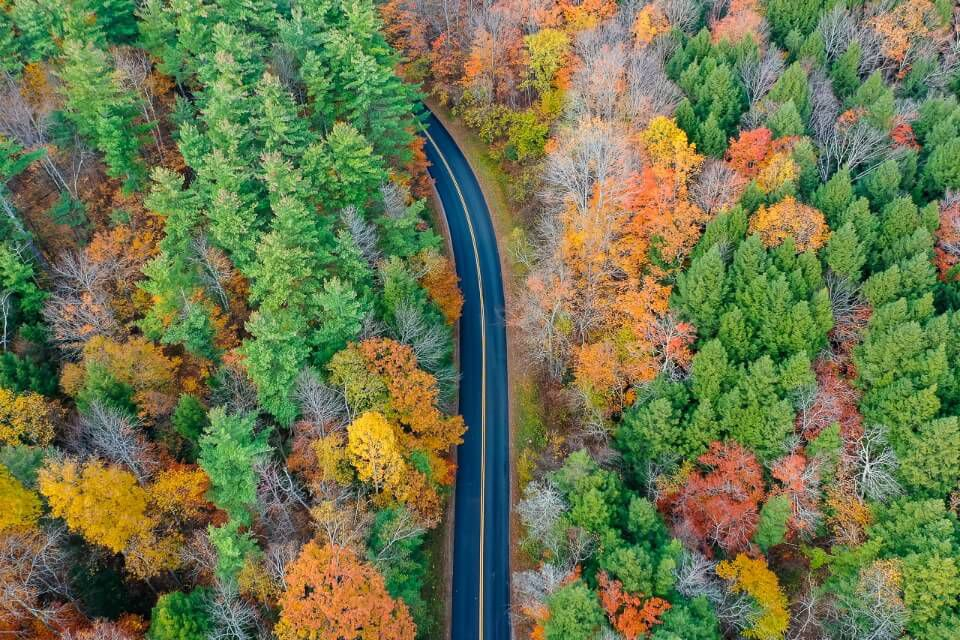 Kancamagus Highway in New Hampshire White Mountain National Forest is one of the most popular roads to drive on a new england fall road trip drone shot stunning colors